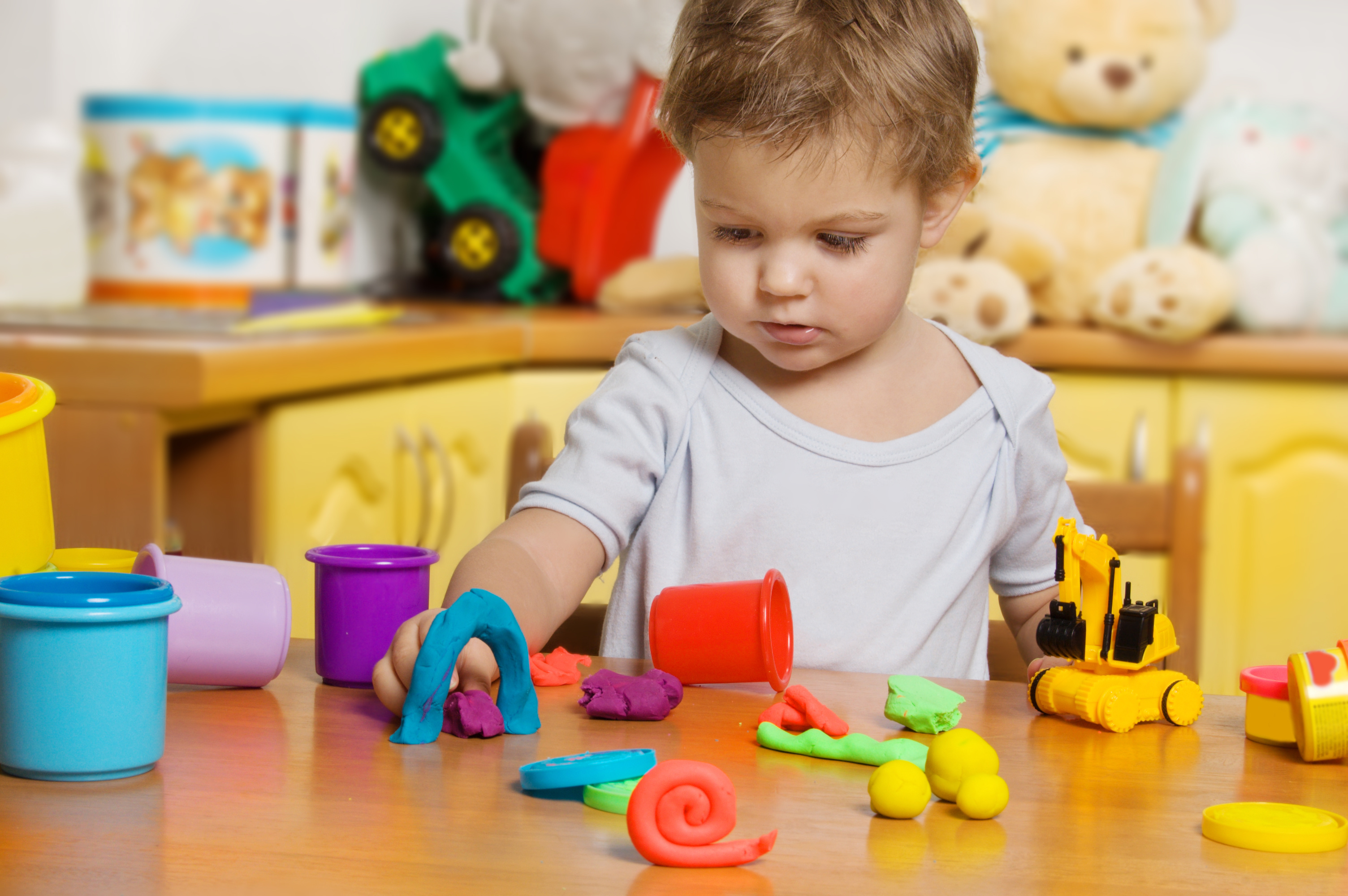 2 years old child playing plasticine in children's room